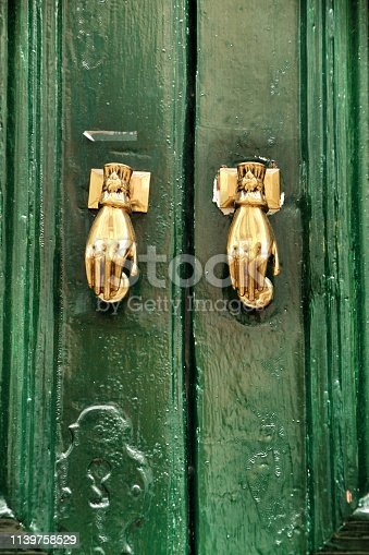 Door knockers with hand shape on green wooden door
