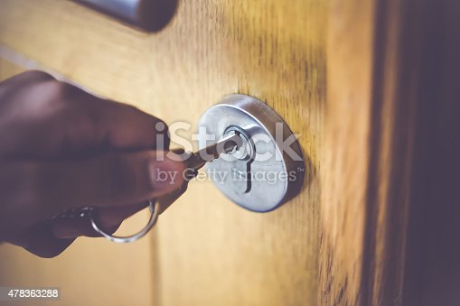 Man opening the door to his home with his steel key.