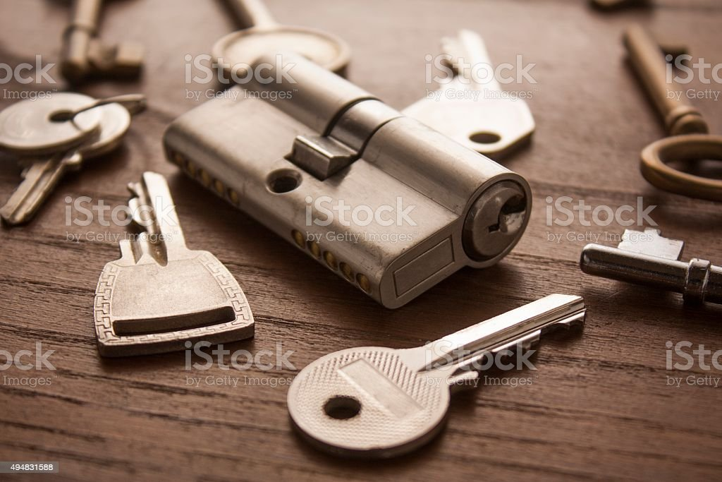 door lock with keys on wooden surface stock photo