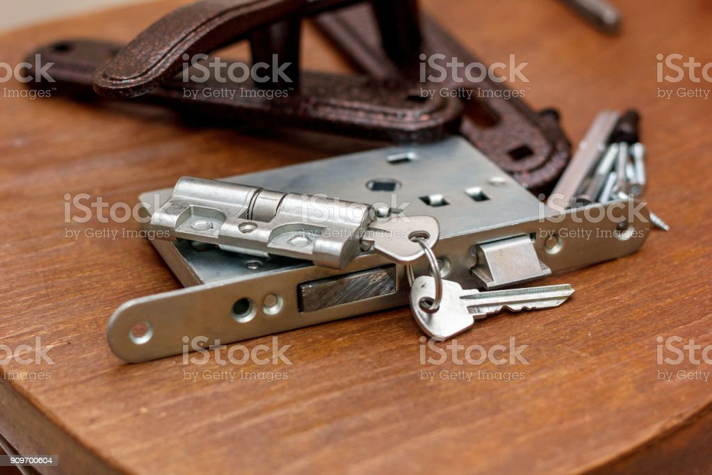 Door lock with keys ready for installation on wooden surface. stock photo