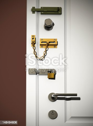 Low angle view on white classic door with several types of DIY safety locks. Scene is lit with a spotlight with small spread for vignetting effect.