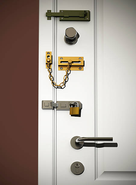 door locks Low angle view on white classic door with several types of DIY safety locks. Scene is lit with a spotlight with small spread for vignetting effect. medium group of objects stock pictures, royalty-free photos & images