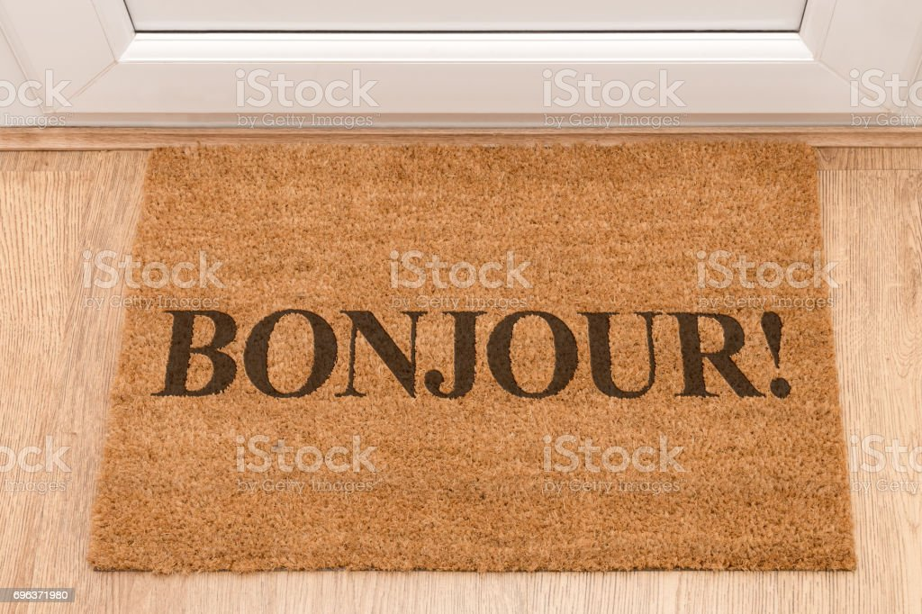 Door mat at front door with Bonjour stock photo
