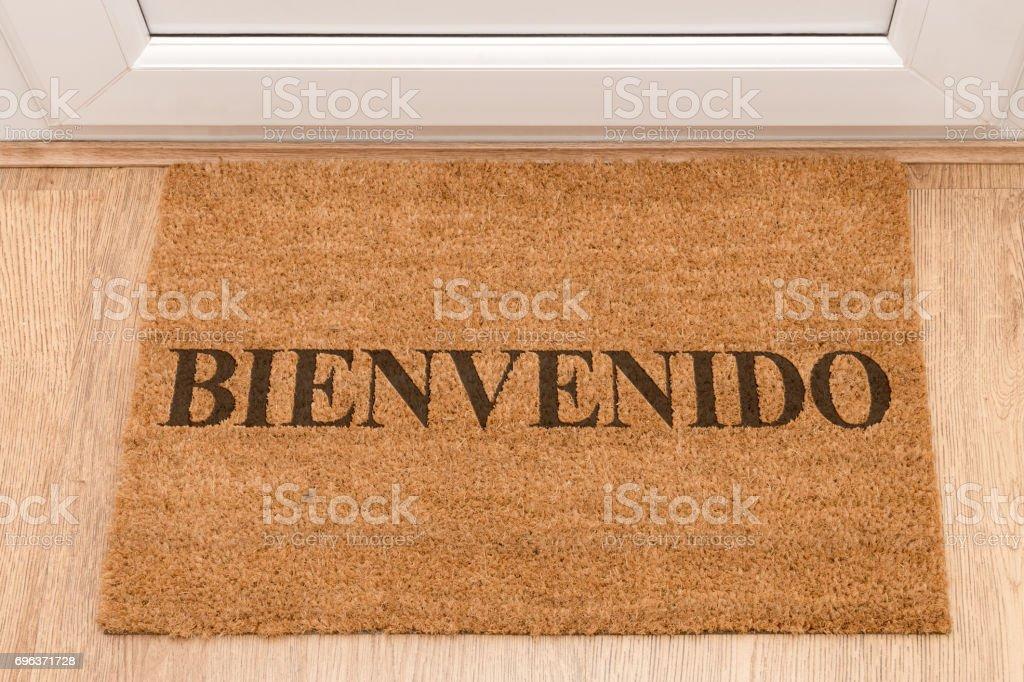 Door mat at front door with Welcome in Spanish - Bienvenido stock photo