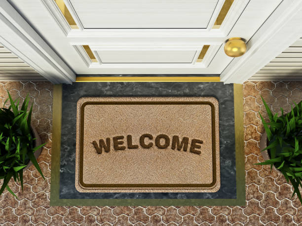 door mat with welcome word standing in front of the house door - guest stock pictures, royalty-free photos & images