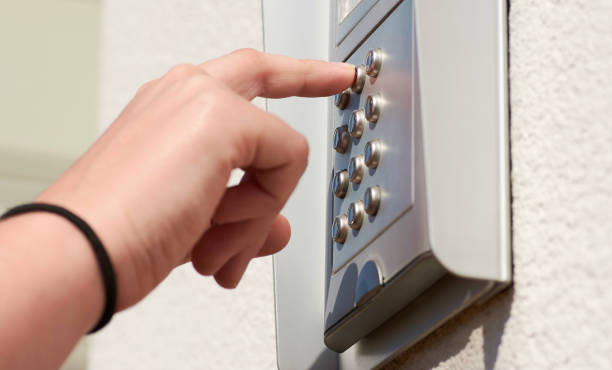 Door numeric encoding device on the building, with female hand holding buttons stock photo