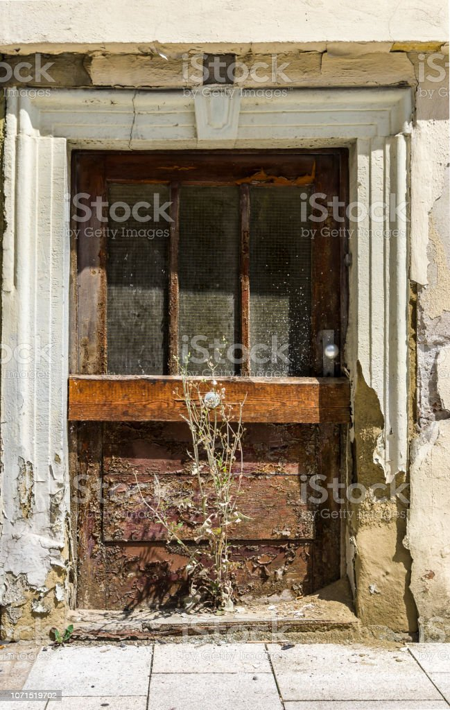 Door of abandoned, dilapidated house and weeds growing in front of...
