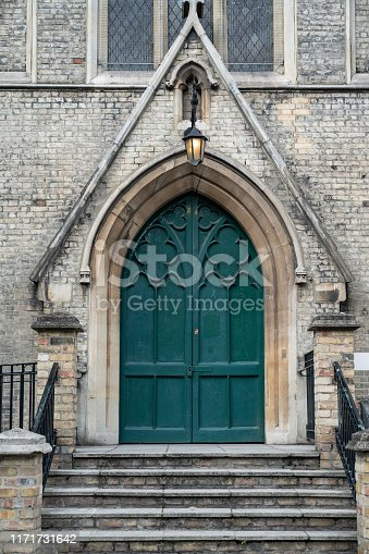 Wooden green door of St John's Church, Stratford, London, Uk. No people are seen in frame. Shot under daylight with a full frame mirrorless camera.