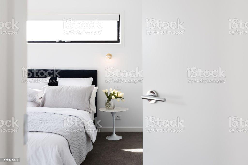 Door opening to reveal a luxury master bedroom stock photo