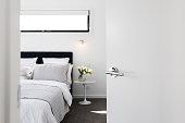 Door opening to reveal a luxury master bedroom