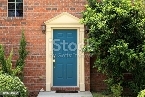close up wooden door from a brick house.