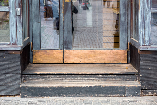 door step at the entrance to an old restaurant with a wooden facade and glass windows with a worn threshold old european architecture close-up