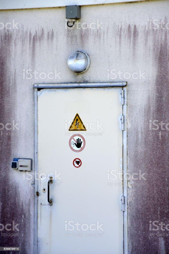 Porta para instalações seguras com perigo, não entre sinais. - foto de acervo