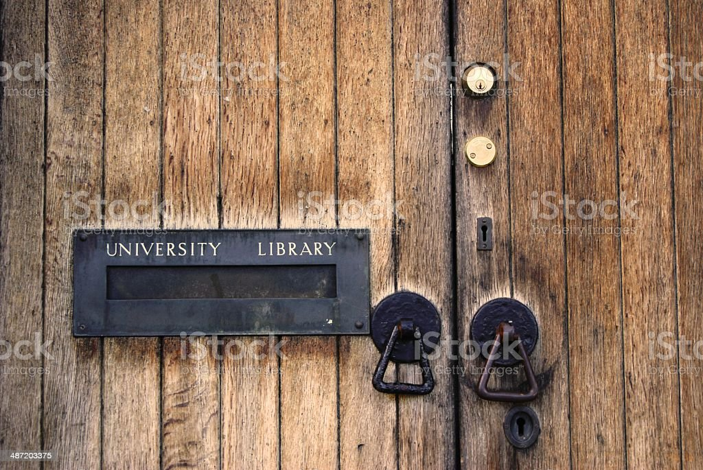 Door to the University Library Wooden door with vertical planks, a brass postbox with the words University Library in gold letters and several copper handles and locks Alphabet Stock Photo