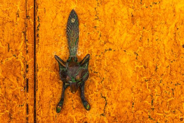 Porta com aldrava de bronze em forma de uma raposa, bela entrada para a casa - foto de acervo