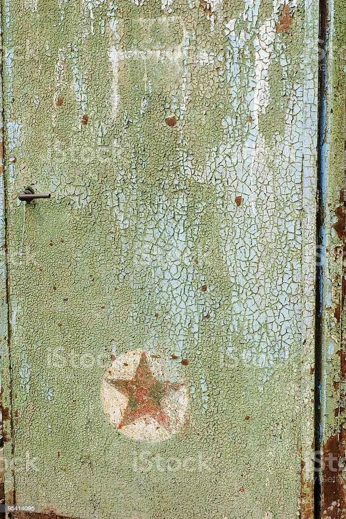 Door with cracked paint and red star royalty-free stock photo