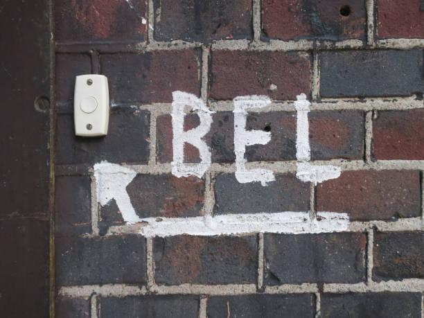deurbel met een teken van een pijl die naar de bel op een muur in Amsterdam bijwonen foto