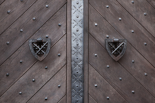 Doorknockers on the wooden gate fixed with rivets