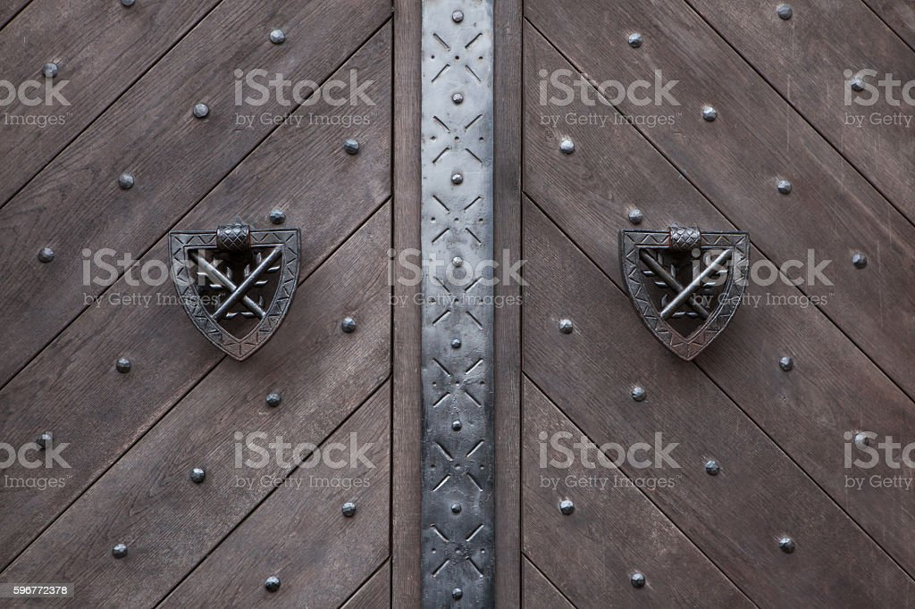 Doorknockers on the wooden gate fixed with rivets stock photo
