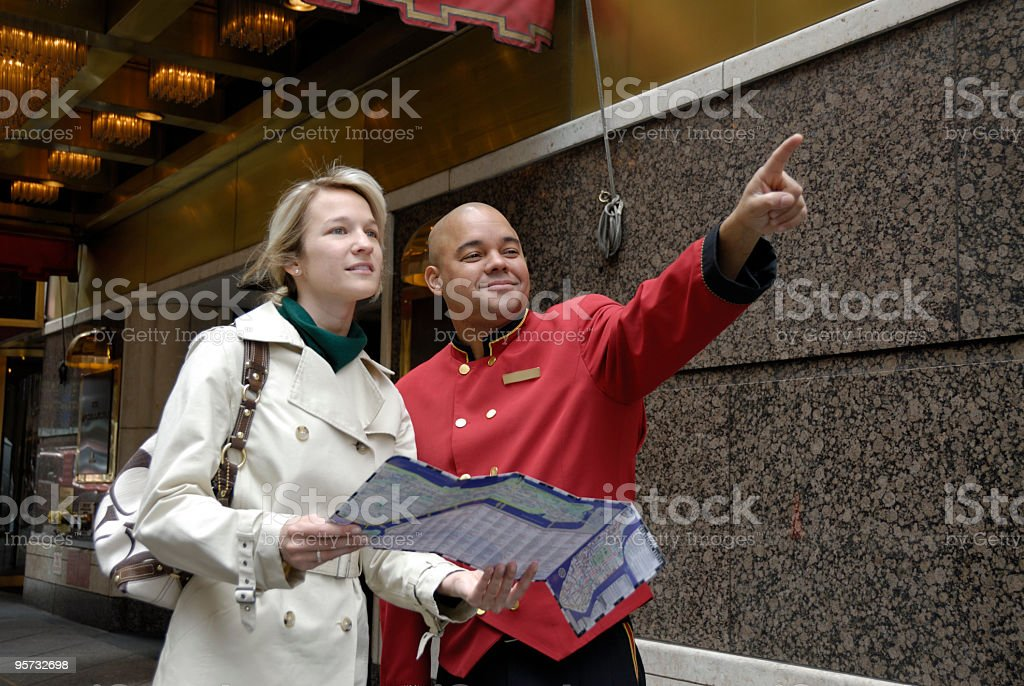 Doorman giving directions to a woman on a street royalty-free stock photo