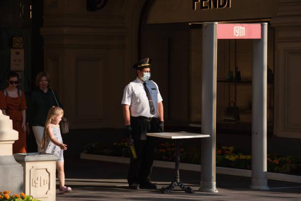 Porteiro-segurança em uma máscara médica perto da entrada do GUM em Moscou - foto de acervo