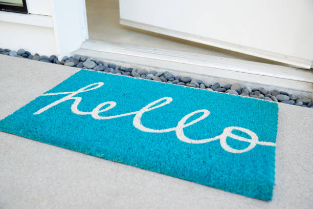 Doormat Outside Open Front Door Of House stock photo