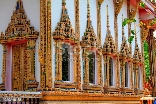 Doors and windows of the temple adorned by intricate wooden carvings in golden color depicting Buddha's life familiarized by Jataka Tales, at Ban Bung Sam Phan Nok, Phetchabun, Thailand