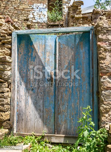 Old wooden door with cracked blue paint. Wild stone fence around an abandoned house in the mountains