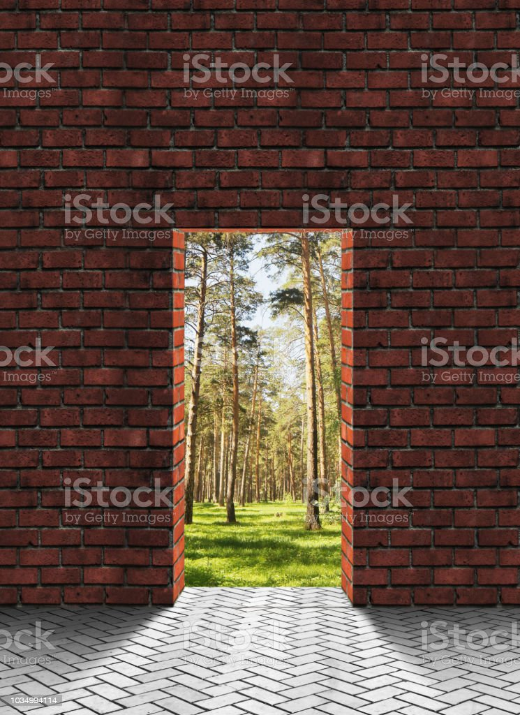 Doorway in the brick wall behind which are nature and pine forest. Exit to freedom stock photo