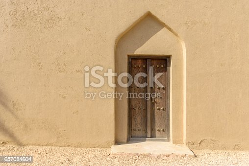 Doorway in an arabian fort with old wood door contrasting with the mud walls