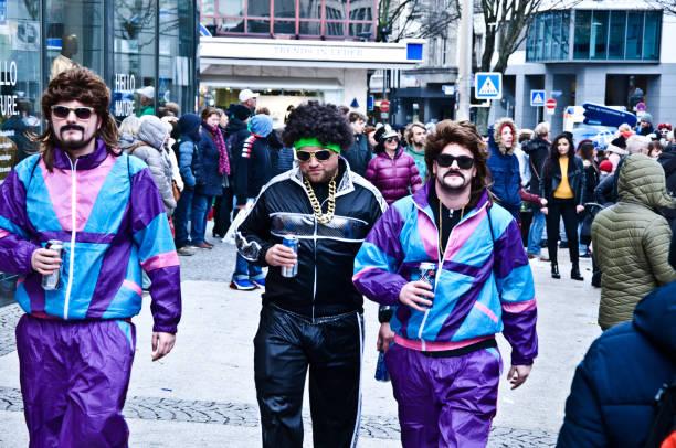 dortmunder rosenmontag purple blues brothers an der kampstraße: bunt gekleidete zuschauer/touristen genießen den dortmunder rosenmontag (rosenmontag)-höhepunkt des deutschen karnevals, am faschingsmontag vor aschermittwoch - bier kostüm stock-fotos und bilder