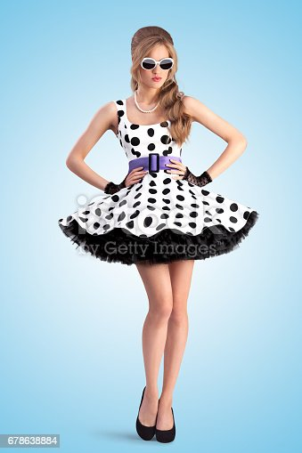 Creative photo of a vogue pin-up girl, dressed in a retro polka-dot dress and sunglasses, posing on blue background.