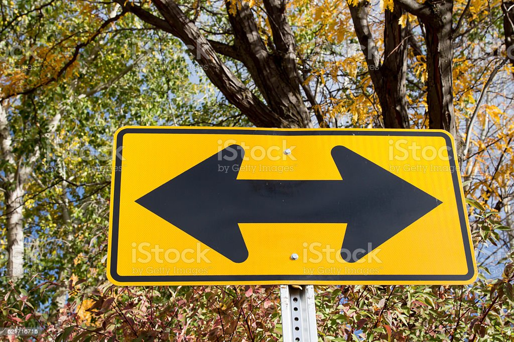 Double arrow caution traffic sign in the autumn stock photo