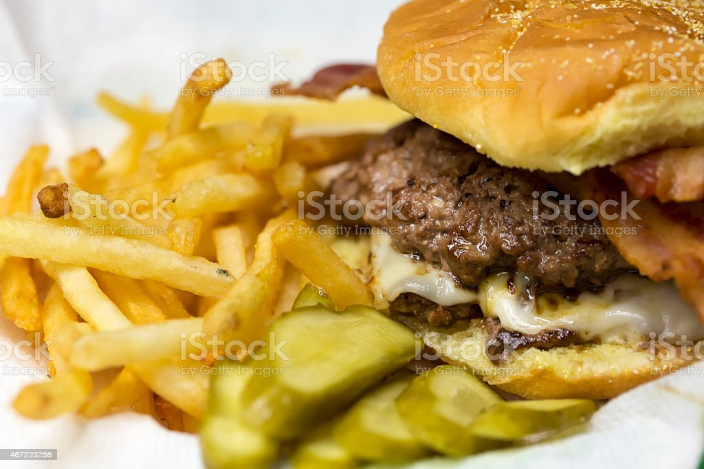 Double bacon cheeseburger with fries and pickles . stock photo