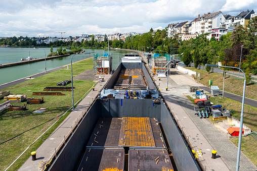 Double barge filled with sheets of thick metal, flowing into the river lock.