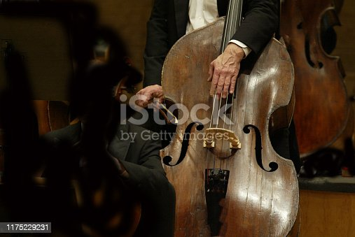 A man's hand touches the strings of an old double bass musical instrument