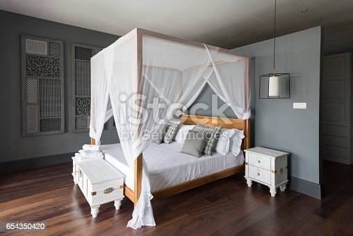 Bedroom in luxury villa with grey walls and white furniture