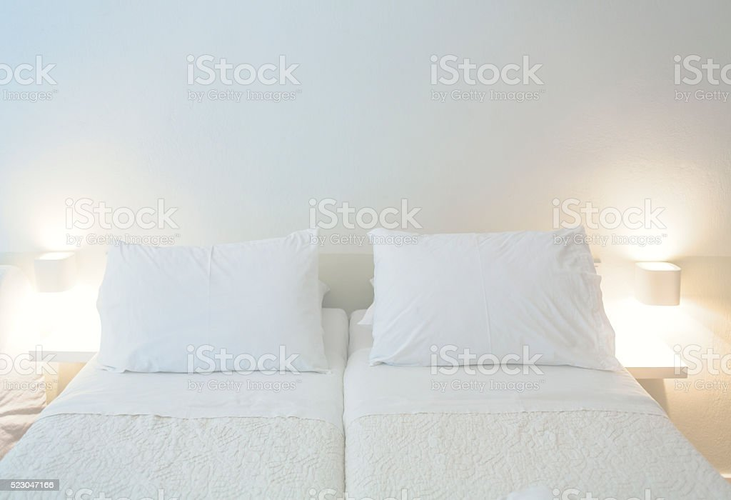 Double bed in simple white room stock photo