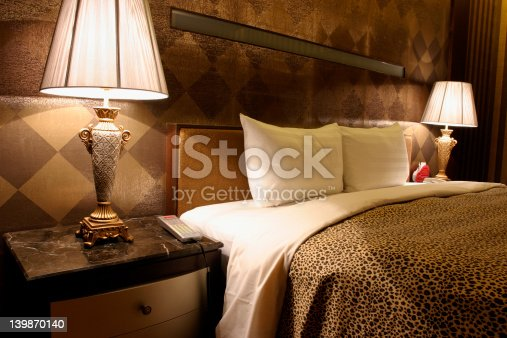 Double bed in hotel room with warm light.