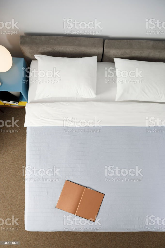 Double bed. Retro style hotel bedroom. Directly Above. Weekend Activities, Book In Bed. stock photo