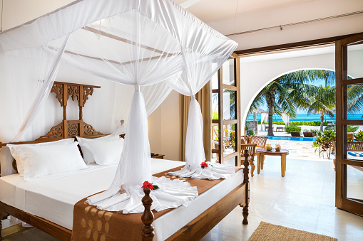 Double bed with mosquito net in luxury bedroom in holiday villa (Zanzibar, Tanzania). Property released.