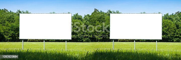 istock Double blank advertising billboard immersed in a rural scene - image with copy space 1092620684