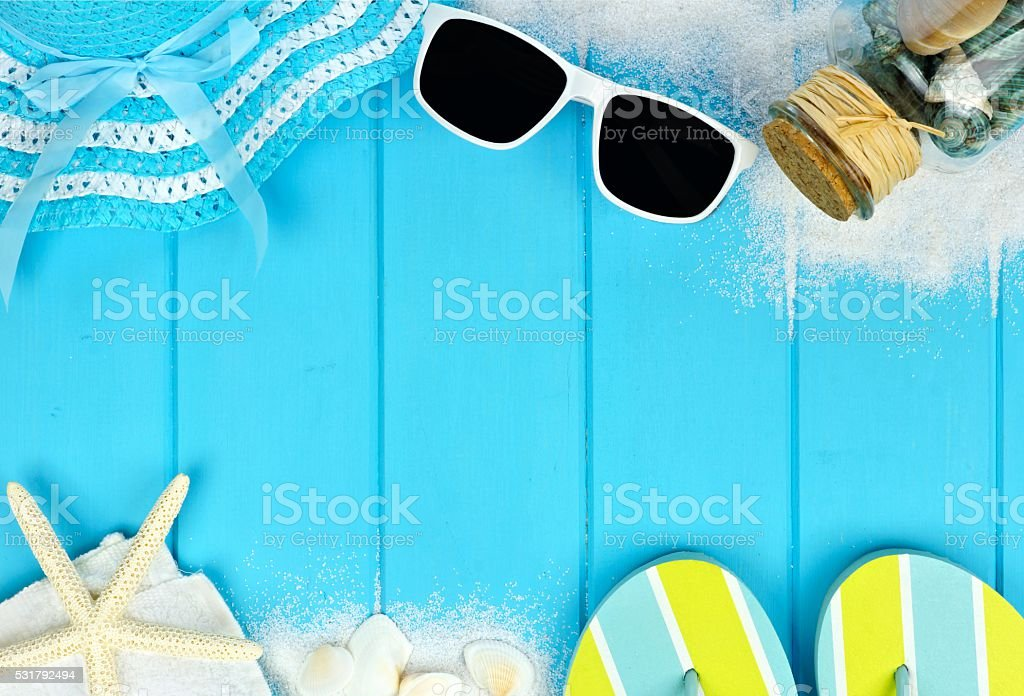 Double border of beach items and seashells on blue wood stock photo