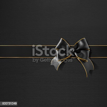 Double bow gold rimmed black ribbon on black texture gift paper