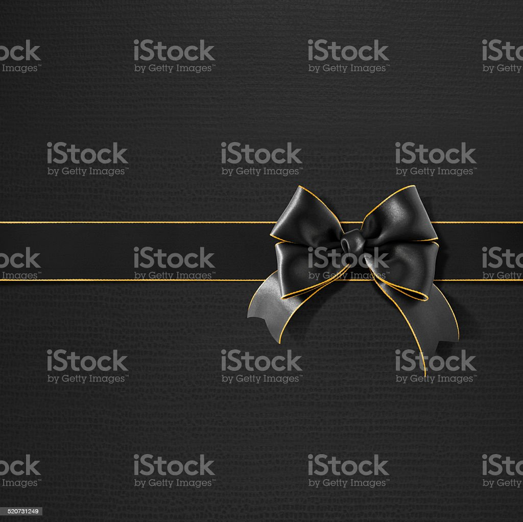 Double bow gold rimmed black ribbon on black gift paper stock photo