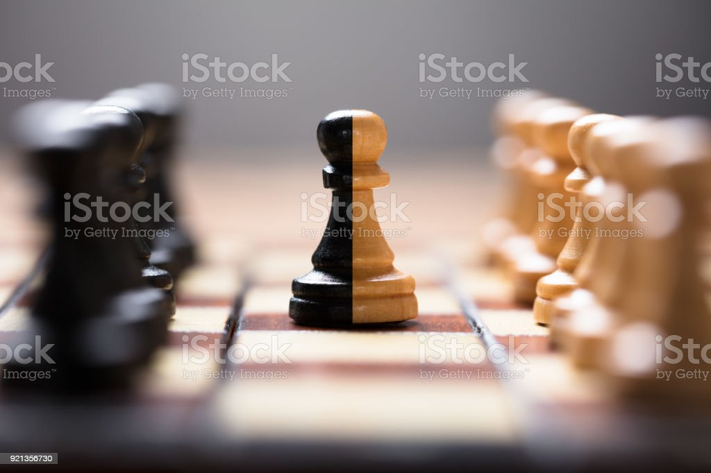 Double Color Pawn Amidst Other Chess Pieces On Board Closeup of double color pawn amidst other chess pieces on board game Agreement Stock Photo