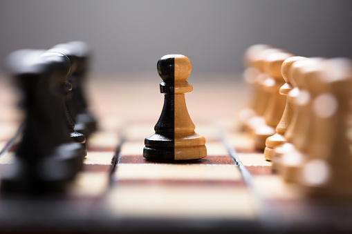 Double Color Pawn Amidst Other Chess Pieces On Board Stock Photo - Download Image Now