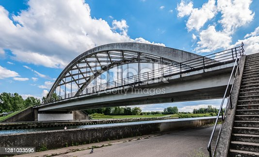 Bright image with modern bowstring bridge over the Nete Canal in Viersel, Zandhoven, province of Antwerp, Belgium. On the side concrete staircase to the bridge. Blue sky and white clouds.