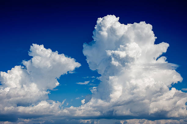 Double cumulonimbus cloud in a deep blue sky stock photo