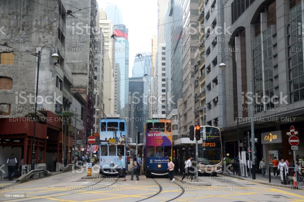 Double Decker Tram on King's road, Sai Ying Pun, Hong Kong island People crossing King's road by two old double decker trams in Sai Ying Pun, an area in the Western District, in the northwestern part of Hong Kong Island. Building Exterior Stock Photo